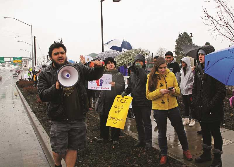 INDEPENDENT PHOTO: JULIA COMNES - Luis Cisneros (left) of the Oregon DACA Coalition leads the approximately 70 attendees of the ICE Out of Wooodburn rally in a chant.