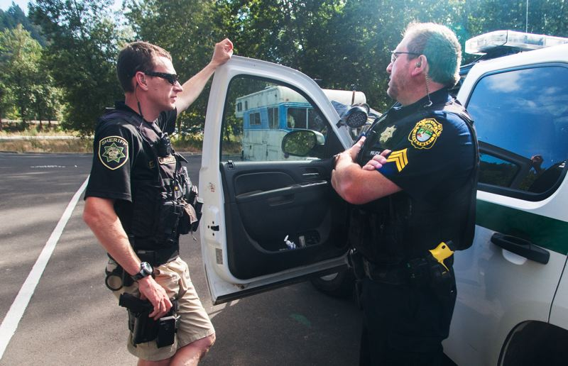 FILE PHOTO: JOSH KULLA - Sheriff's Deputy Kent Krumpschmidt, left, assists Sgt. Rodney Wilkerson in 2015 as they examine an abandoned vehicle at the Sandy River Delta State Park.