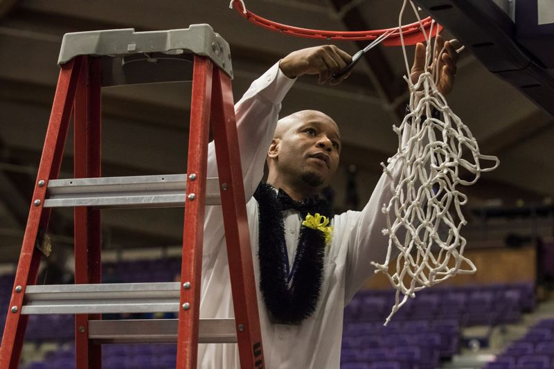 TRIBUNE PHOTO: JONATHAN HOUSE - Jefferson High boys basketball coach Pat Strickland cuts down a net after the Democrats' victory over Clackamas in the Class 6A championship game at Chiles Center.