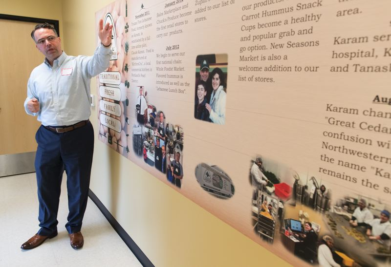 TIMES PHOTO: JAIME VALDEZ - Trazza Fine Lebanese Food owner Claude Karam shows a timeline of his business, from its beginnings in 2011 to the present day, on the wall of its new production facility in Tualatin.