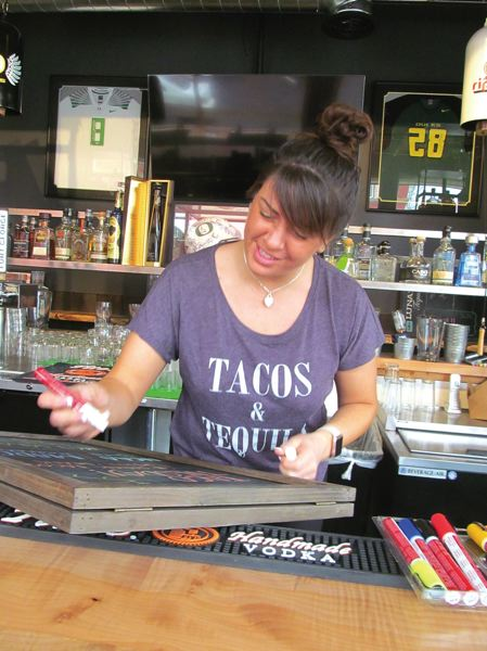 PHOTO BY ELLEN SPITALERI - Kara Castillo, co-owner of downtown Oregon Citys Mesa Fresca, finishes writing the days specials on a blackboard. Taco Tuesday is popular with diners.