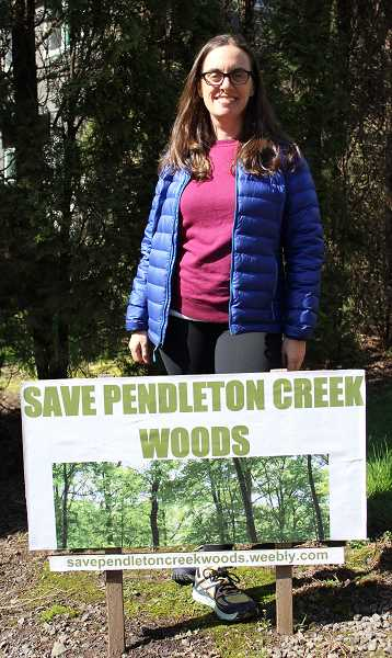 CONNECTION PHOTO: HANNAH RANK - Randi Sachs, who lives directly across from the proposed development site, has been a vocal opponent of the current plan. Here she poses in front of her 'Save Pendleton Creek Woods' sign.