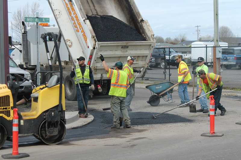 PIONEER PHOTO: CONNER WILLIAMS  - Houck Construction crews hurry last Thursday to finish paving the final layer on Molalla Avenue before rain returns.