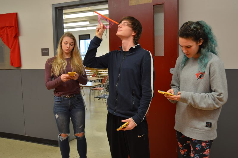 SPOTLIGHT PHOTO: NICOLE THILL - Scappoose High School sophomores Jenna Hatcher, Kyle Johnson and Jordyn Hall work on an assignment for their math class using new scientific calculators that were donated to the high school Wednesday, March 22. Previously, students used their phones to make calculations.