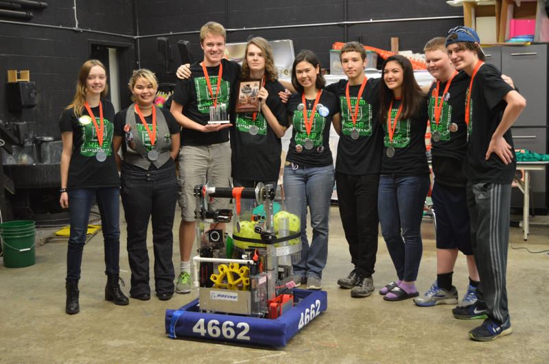SPOTLIGHT PHOTO: NICOLE THILL - Some members of the Scappoose High School robotics club, called Byte Sized, pose with their competition robot after taking a second-place victory at Clackamas Academy of Industrial Arts. The team will head to the next competition on Friday, March 31, at Lake Oswego High School.