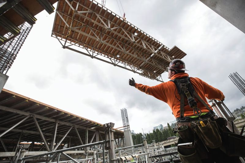 PAMPLIN MEDIA GROUP: JON HOUSE - A construction worker waits for a deck to be lowered as a tower crane flies a table up to what will be the third floor at the site of the new Knight Cancer Research Building.