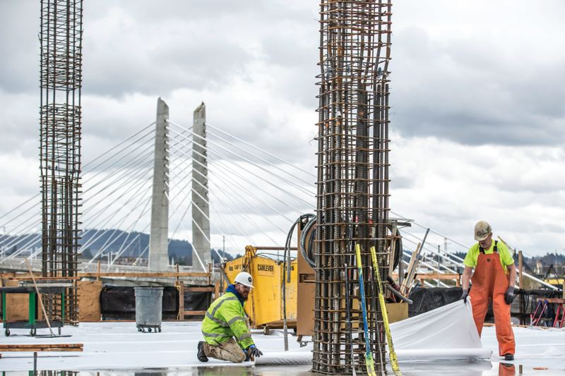PAMPLIN MEDIA GROUP: JON HOUSE - Workers lay sheeting on newly-poured concrete at the Knight Cancer Research Building site to protect it from the weather, saving time and money. 'The $50,000 to tarp the building saves seven weeks, which was $25,000 a day in general conditions or $850,000 a week,' Howard said. 'That's amazing thinking.'