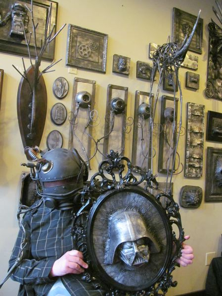 PHOTO BY ELLEN SPITALERI - Chris Truax dons a steampunk-ish helmet while holding a piece depiciting Darth Vader, frozen in time.