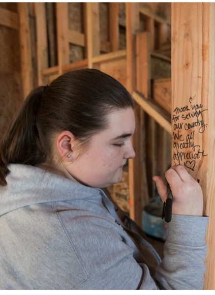 """TIMES PHOTO: JAIME VALDEZ - Heidi Gettinger, 16, writes a message on the wood of the new home of retired U.S. Army Sgt. Wade Mitcheltree during the """"Walls of Honor"""" event held by the Gary Sinise Foundation. Gettinger is a neighbor of the family."""