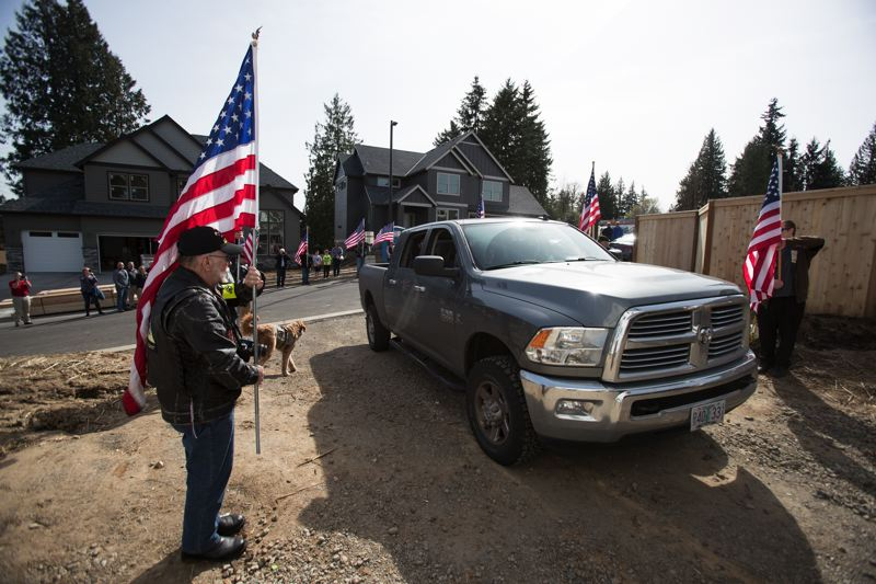 """TIMES PHOTO: JAIME VALDEZ - The Patriot Guard Riders hold American flags as they escort welcome retired U.S. Army Sgt. Wade Mitcheltree and his family to his new home during the """"Walls of Honor"""" event held by the Gary Sinise Foundation."""