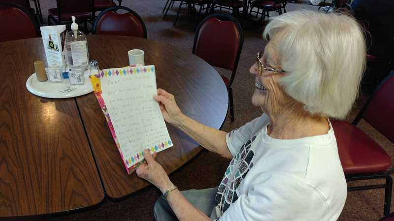 NEWS-TIMES PHOTO: STEPHANIE HAUGEN - Writers in the Grove member Lela Baskins reads through one of the letters she got from her pen pals at Gaston Elementary School.