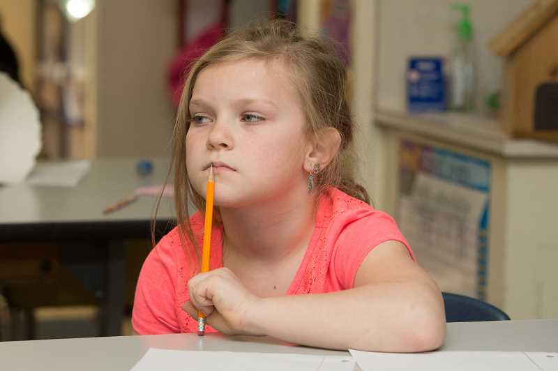 Fayth Sanders, 7, listens to her teacher read a letter to the class from one of their Forest Grove pen pals.