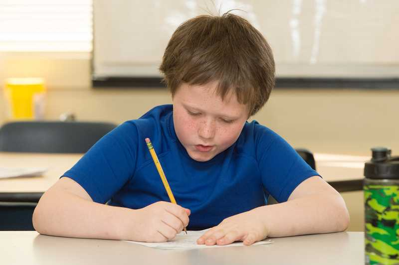 NEWS-TIMES PHOTO: CHRISTOPHER OERTELL - Dalton Wold, 8, a second-grader at Gaston Elementary, works on a letter to his Forest Grove pen pal.