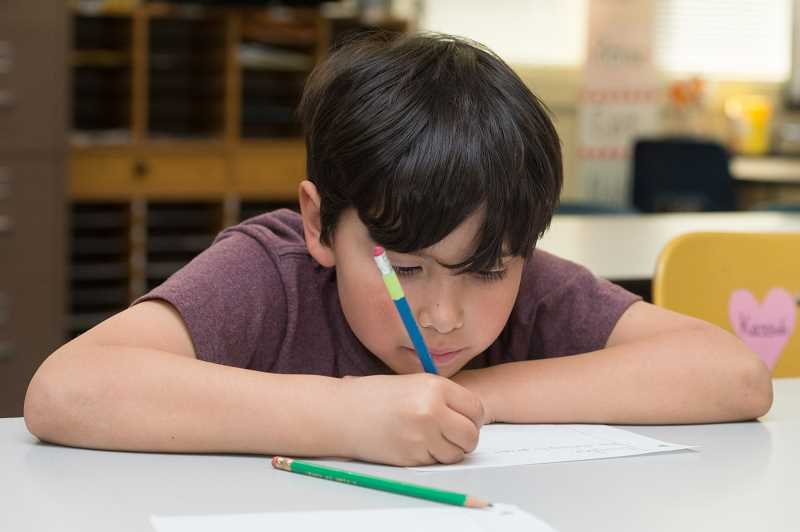 NEWS-TIMES PHOTO: CHRISTOPHER OERTELL - Anthony Benitez, 8, concentrates deeply while writing to his pen pal, Bev Walker.