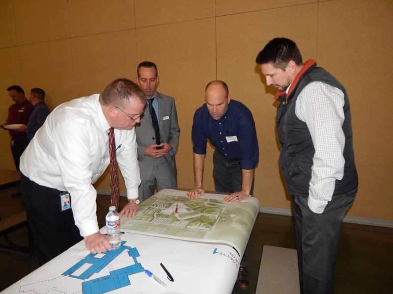 BARBARA SHERMAN - A group looking at the new Sherwood HIgh School site concept master plan at an April 3 community meeting includes (from left) School Board Director Pat Allen and SSD Assistant Superintendent Gary Bennett.