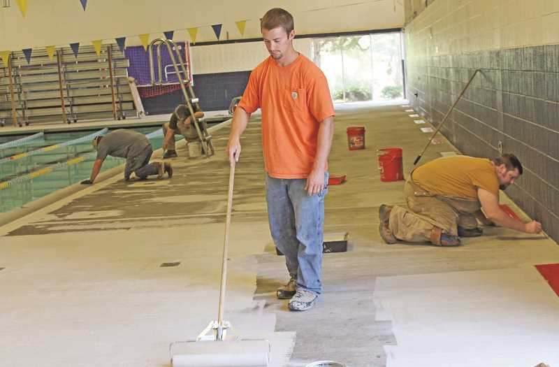 REVIEW FILE PHOTO: JILLIAN DALEY - Workers lay down a coat of sealant on the Lake Oswego School District pool's concrete flooring during a maintenance blitz in the summer of 2014. From left: Phil Williams, Tom Williams, Phil Oppen and Josh Williams