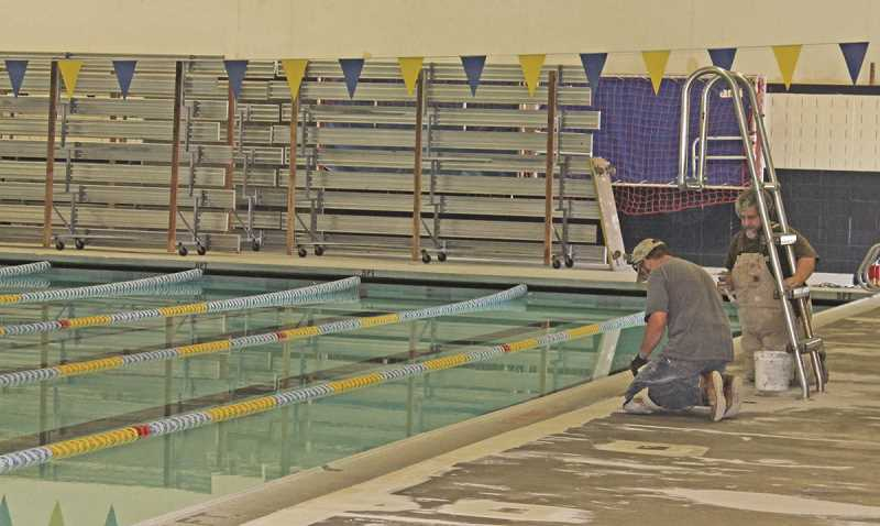 REVIEW FILE PHOTO: JILLIAN DALEY - Phil Williams and Tom Williams were among several people working on major upgrades at the Lake Oswego School District pool back in the summer of 2014.
