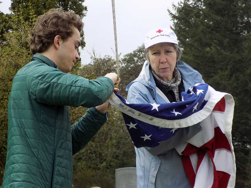 GAZETTE PHOTO: RAY PITZ - Boy Scout Dawson Durig of Wilsonville and Charlotte Lehan, webmaster for Pleasant View Cemetery and a member of the Wilsonville City Council, prepare to raise a flag at the cemetery on April 6.