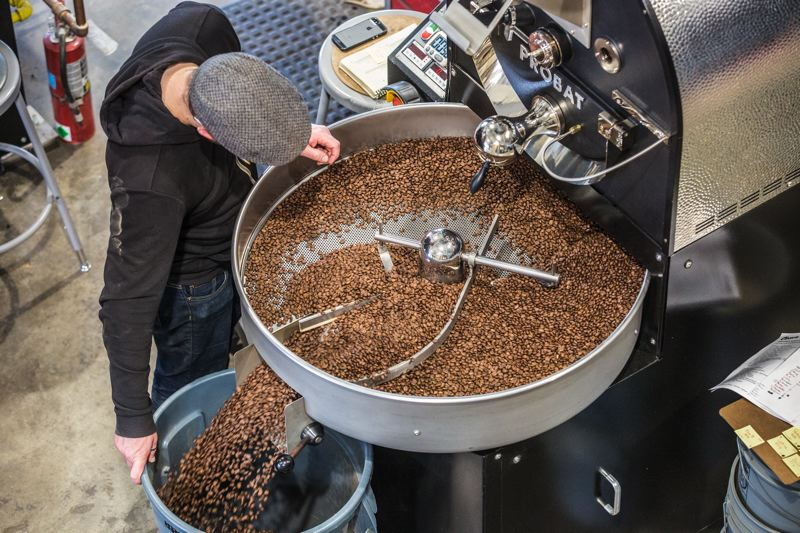TRIBUNE PHOTO: JONATHAN HOUSE - A Coava Coffee worker checks to see if coffee beans have finished roasting at their new headquarters. Boss Higgins prefers high quality  Probat machinery, and helped customize and install it.