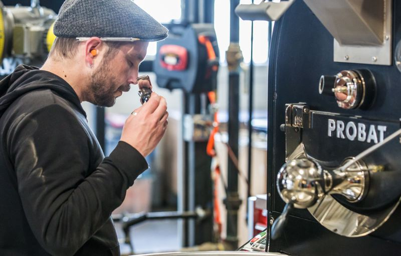 TRIBUNE PHOTO: JONATHAN HOUSE - Coava Coffee's Justin Swanson checks to see if coffee beans have finished roasting at their new headquarters.Boss HIggins prefers high quality  Probat machinery, and helped customize and install it.