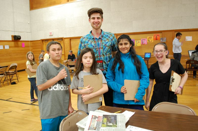 PHOTO BY: LACEY BRODERS - Riverside Elementary students, from left, Darin Vestal, Phoenix Hout, Sarah Jimenez and Bethany King celebrate the completion of a news story about Thursday's career fair with Raymond Rendleman, Clackamas Review news editor.