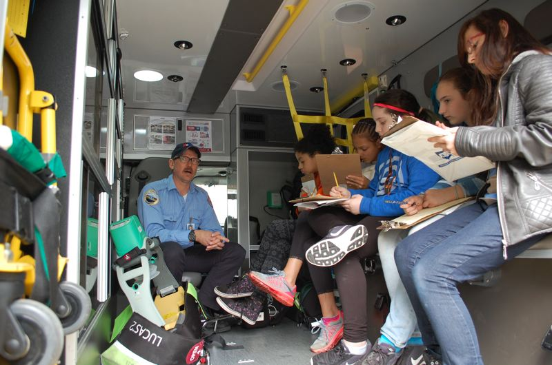 PHOTO BY: LACEY BRODERS - American Medical Response paramedic Barry Morgan shows students at Riverside Elementary School the inner workings of an ambulance.
