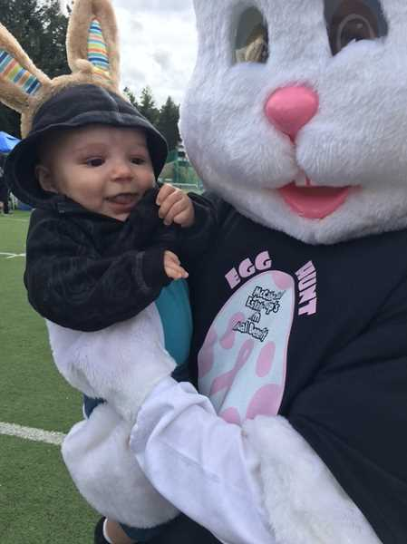 COURTESY OF LESLIE MCCABE - The Easter Bunny gives a huge to 4-month-old Lincoln during the  11th McCabe Real Estate Groups Annual Benefit Egg Hunt held at Sherwood High School on April 8.