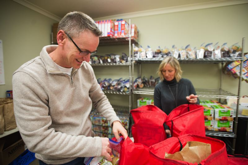 OUTLOOK PHOTO: JOSH KULLA - Lead Pastor Jay Messenger and Outreach Ministries Leader Rhonda Patrick prepare backpacks full of food for low-income students at East Gresham Elementary School.