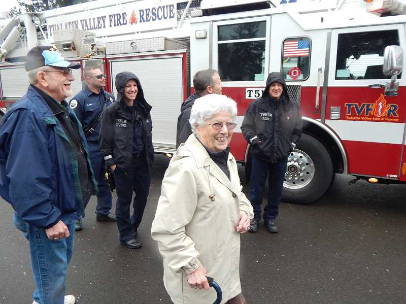 REGAL COURIER PHOTO: BARBARA SHERMAN - (From left) In the parking lot of Tigard American Legion Post 158, an American Legion member watches the action along with Nathan Kust, TV&R firefighter/EMT and driver of T51; Kim Haughn, TV&R public information officer; Patsy Nestor; Craig Lyon, captain of Station 51; and Mark Ross, firefighter/paramedic.
