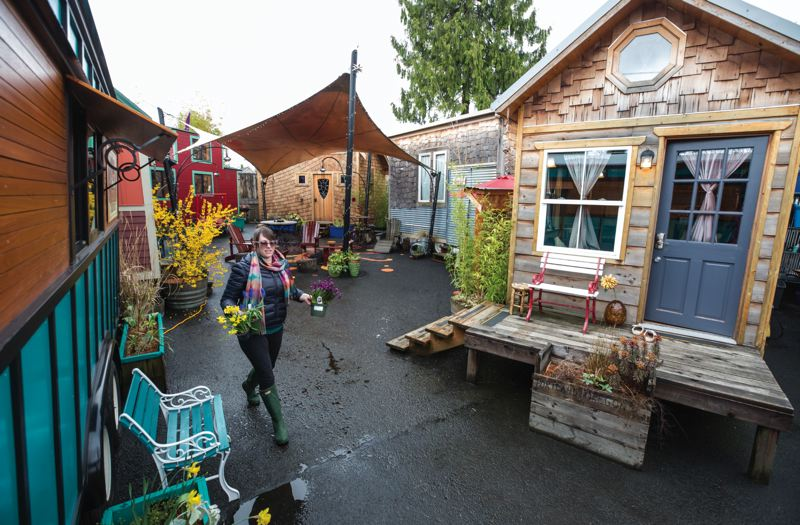 TRIBUNE PHOTOS: JONATHAN HOUSE - Heidi Cain gets ready to plant flowers at Caravan, the Tiny House Hotel on Northeast Alberta Street, one of the first places in a U.S. city where tiny houses were legal for habitation.