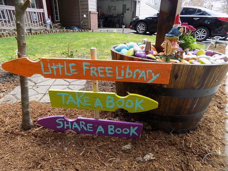 GAZETTE PHOTO: RAY PITZ  - Rebecca King and her girls added festive signs to their new small library, which can contain between 50 and 100 books, located at the end of Redfern Drive next to the nature park trail.