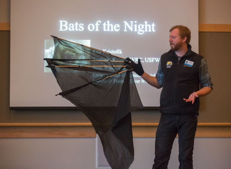 TIMES PHOTO: JONATHAN HOUSE - Seth Winkelhake demonstrates how large a bat wing would be if humans had them, during a talk at the Tualatin Library.