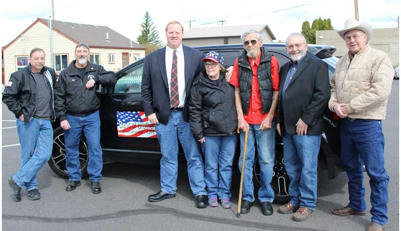 JASON CHANEY/CENTRAL OREGONIAN  - Band of Brothers members join the Crook County Court for a photo in front of the new veterans medical transport vehicle. Pictured left to right are Allen Dendy, Bob Eck, County Judge Seth Crawford, Diane Dendy, Asa Laughlin, County Commissioner Brian Barney and County Commissioner Jerry Brummer.