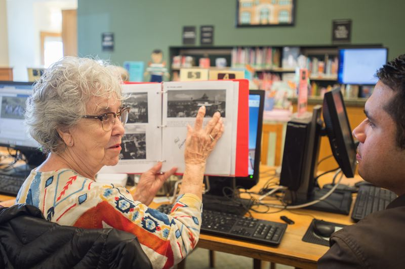OUTLOOK PHOTO: JOSH KULLA - Vonitia Woolsey works on her autobiography with Carlos Galeana recently at the Fairview Library. Galeana is teaching Woolsey to use Google and other digital technologies to help find historical photographs and complete her project.