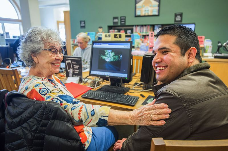 OUTLOOK PHOTO: JOSH KULLA - Vonitia Woolsey and Carlos Galeana share a laugh recently at the Fairview Library, where Galeana is assisting her in putting together an autobiographical book using the latest in digital and Internet technology.