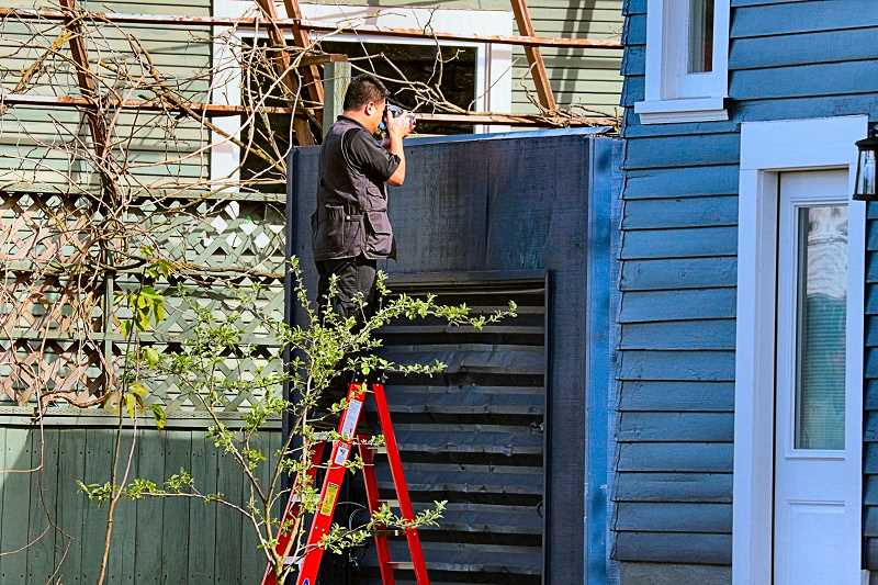 "DAVID F. ASHTON - Using a ladder to see over the top of the garage where the ""person of interest"" was captured, this Forensic Evidence Division member documents the scene."