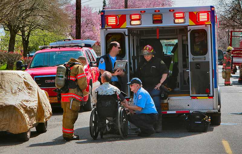 DAVID F. ASHTON - Medical personnel evaluate the occupant of the burning house on S.E. 71st, and provide first aid.