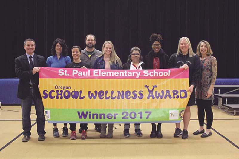 LINDSAY KEEFER - Holding the banner presented at Friday's assembly are (from left) Superintendent/St. Paul Elementary Principal Joe Wehrli, wellness committee volunteer Kim Faber, wellness committee Chairwoman Toni Veeman, P.E. and health teacher Justin Whitlock, teacher Carmen Boyd, head cook Luisa Milera, ODE Director of Child Nutrition Programs Joyce Dougherty, teacher Kristi Stoltenberg and Oregon Dairy Council director of school programs Crista Hawkins.
