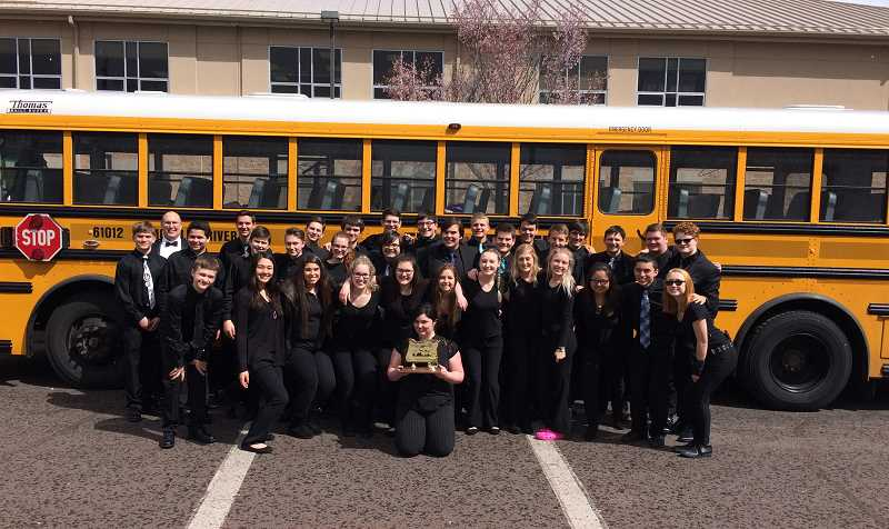 PHOTO COURTESY OF MATT FARRIS - The victorious members of the Molalla High School Wind Ensemble and their director, Matt Ferris (back left), pose with their district trophyfollowing their winning performance at the Tri-Valley Conference last weekend. This is the first time MHS has won the Tri-Valley title.