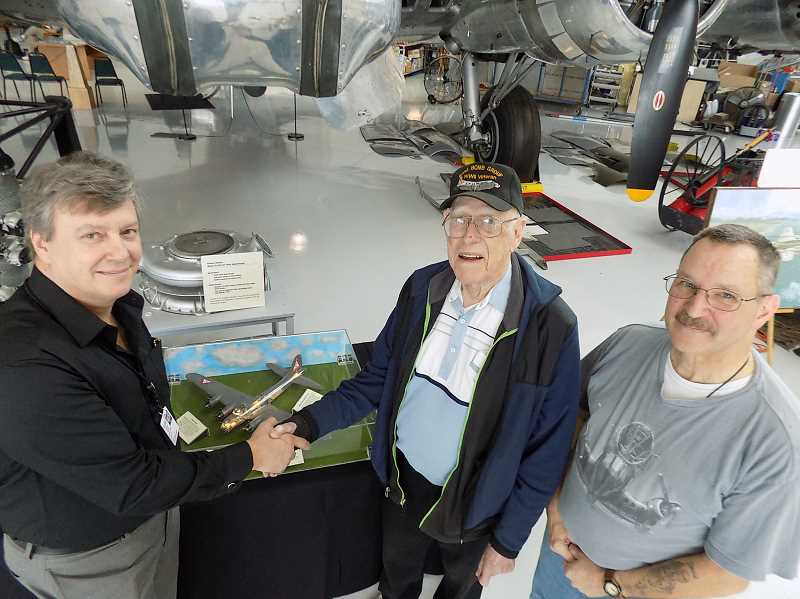 GAZETTE PHOTO: RAY PITZ - Terry Juran, left, curator of the Evergreen Aviation & Space Museum, shakes hands with Don Anderson, a former Sherwood resident, after he donated a scale replica of the B-17 he flew in as a tail gunner during World War II.  David Foss, an award-winning Sherwood model maker, right, built the model, which has extraordinary detailing.