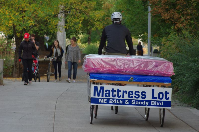 COURTESY MATTRESS LOT - A Mattress Lot employee delivers bedding by bicycle.