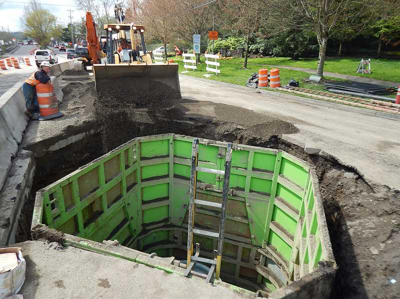 REVIEW PHOTO: ANTHONY MACUK - With the 35-foot-deep central manhole shaft almost completed, workers have begun filling in the edges of the pit they dug to reach the Tryon Interceptor sewer line under Highway 43.