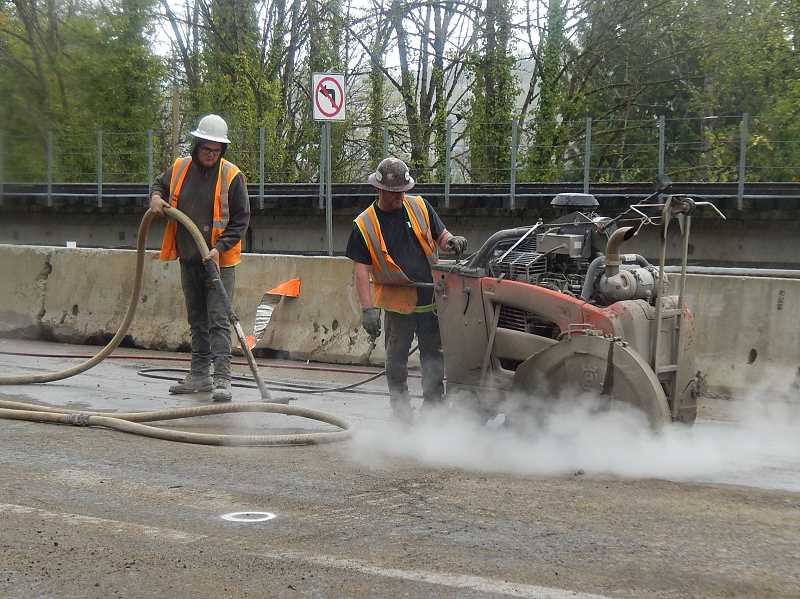 REVIEW PHOTO: ANTHONY MACUK - Portland Bureau of Environmental Services workers cut through the pavement in preparation for digging a trench to install part of a new sewer line under Highway 43.