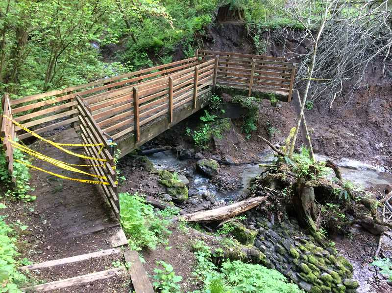 TIDINGS PHOTO: LESLIE PUGMIRE HOLE - Marys Trail in Mary S Young Park has been particularly hard hit in this winters weather-related damage, including a slide that wiped out a bank and this footbridges connection to the trail.