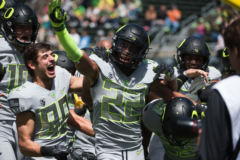 TRIBUNE PHOTO: CHRISTOPHER OERTELL - Oregon Ducks receiver Darren Carrington celebrates with teammates after one of his touchdown catches in Saturday's spring game at Autzen Stadium.