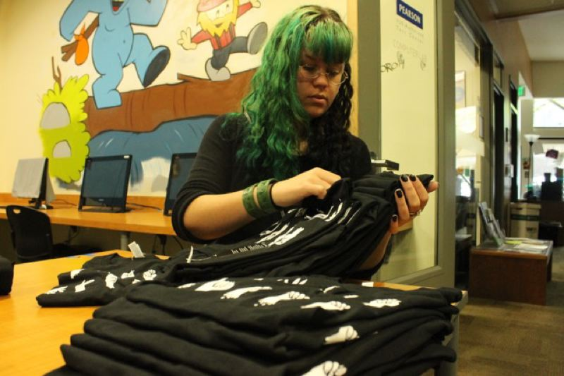TRIBUNE PHOTO: LYNDSEY HEWITT - Olivia Lewis, 22, folds up some of the shirts she helped design to debut at Design Week last week.
