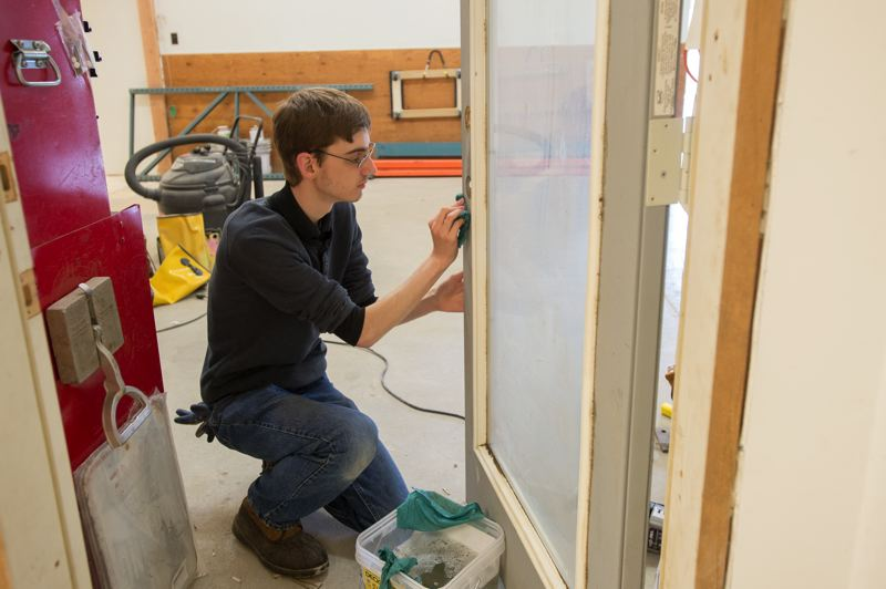 OUTLOOK PHOTO: JOSH KULLA - Habitat for Humanity volunteer and Troutdale resident Jacob Hollis works on a door in the new ReStore resale store in Rockwood as it prepares to open this month to the public.