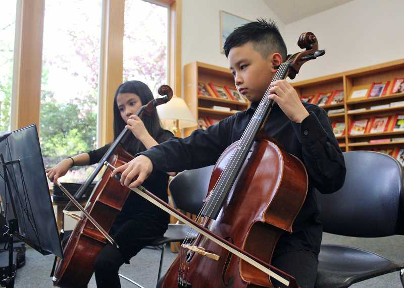 TIDINGS PHOTO: KELSEY OHALLORAN - Lake Oswego 8-year-olds Dannika and Andre Auduong play the cello during a Stafford Chamber Orchestra concert at Wilsonville Public Library April 26.