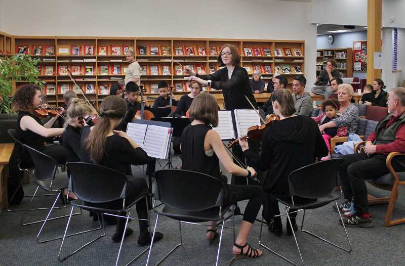 TIDINGS PHOTO: KELSEY OHALLORAN - Maren Knopp conducts the students of Stafford Chamber Orchestra during a concert at Wilsonville Public Library April 26.