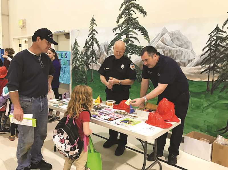 Lieutenant Byron Wakefield of the Molalla Fire District hands out a safety sticker to one of the children attending the Health Fair